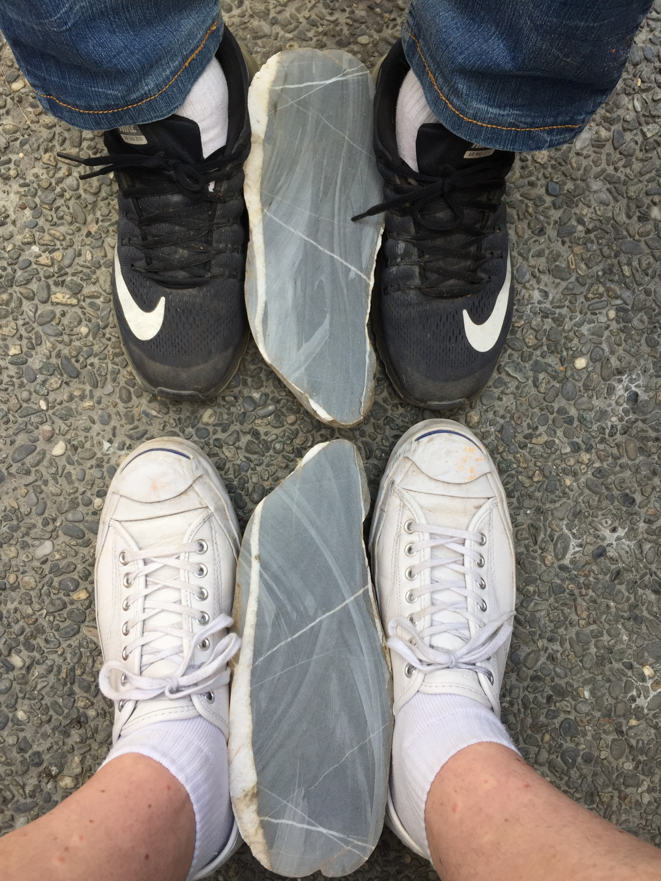 An image of A-Fu and David Clarke starting a residency at NTCRI, a large cut stone between each others feet.