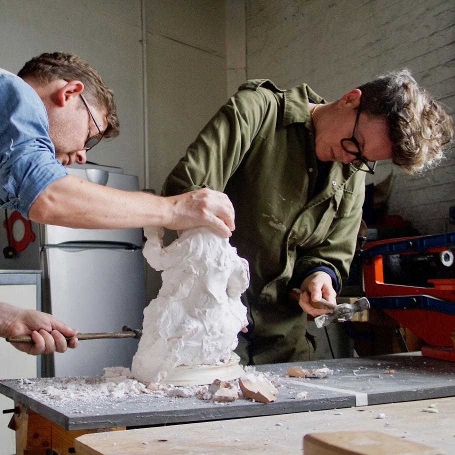 Tracey Rowledge and David Clarke both hammering plaster from a cast figurine in the workshop.