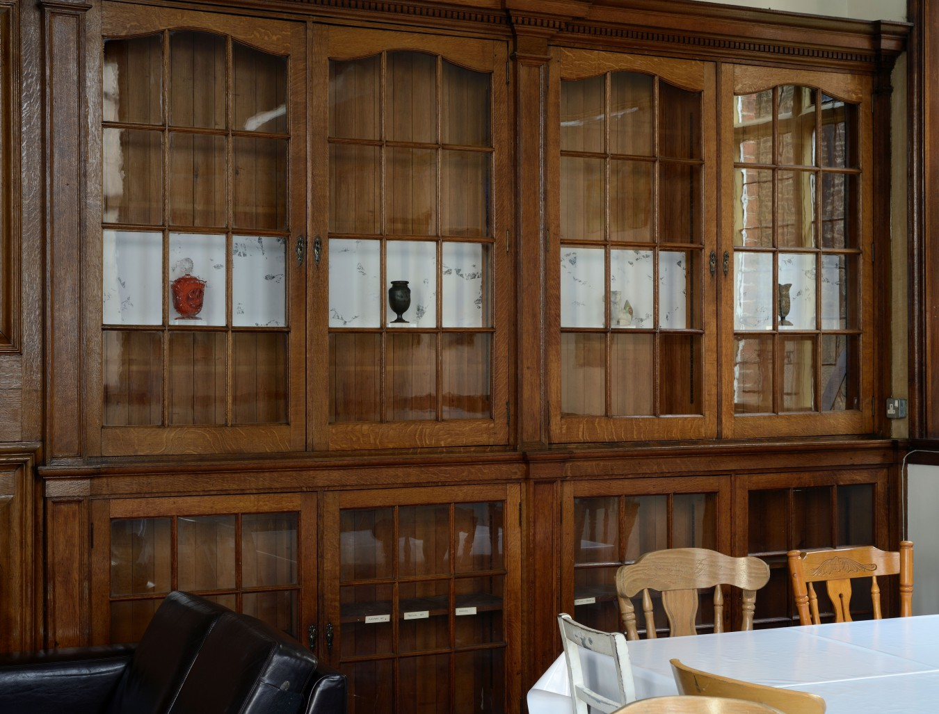 Cafe installation with 4 objects and a drawing in oak book cases.
