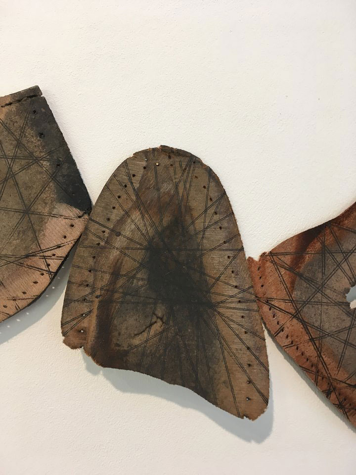 'Lost Souls', old leather shoe soles with carbon lines, hung with a single gold tack.