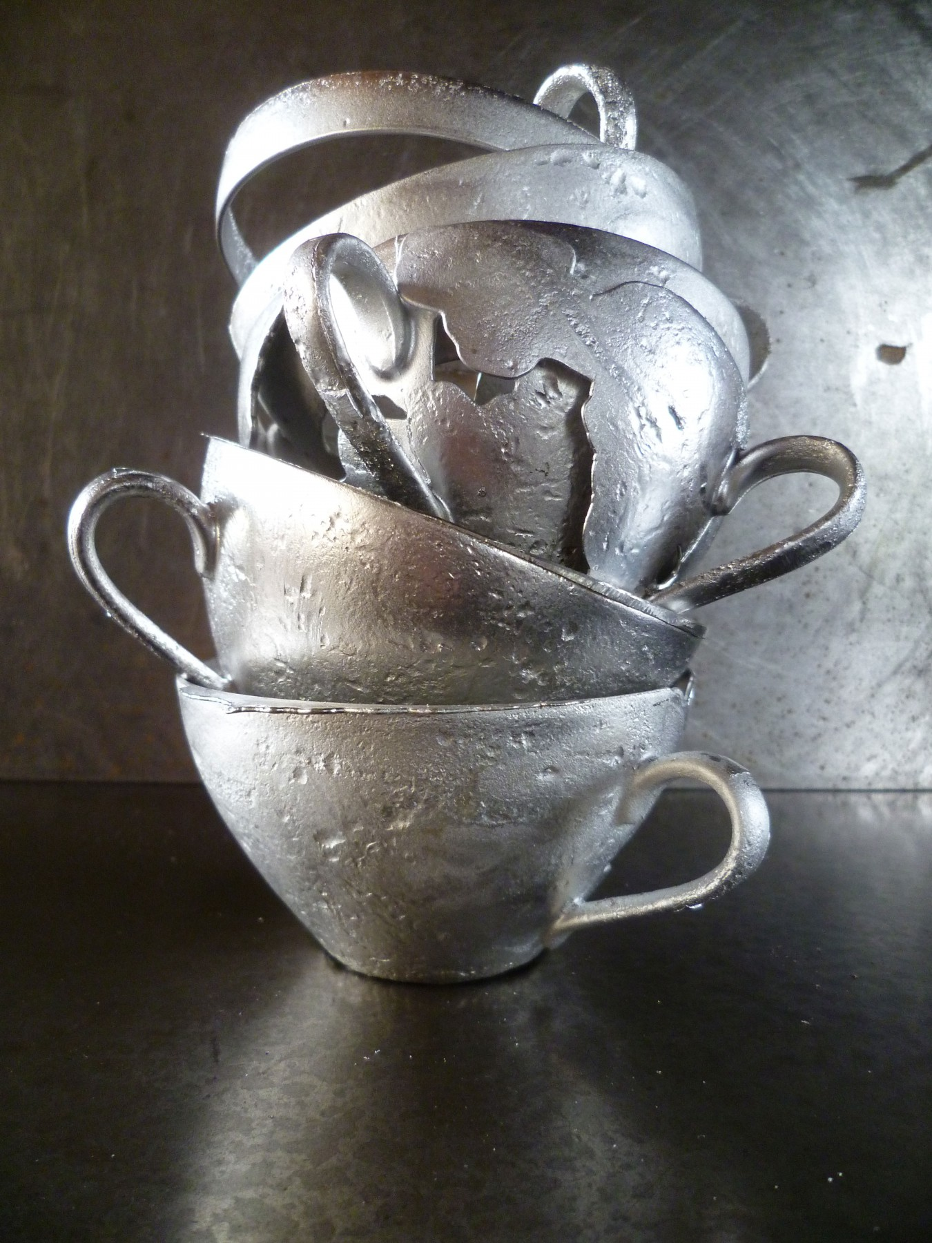 Image of a series od stacked cast metal tea cups. The cup form diminishes the futher up the stack you go. 50% lead and 50% is the alloy.