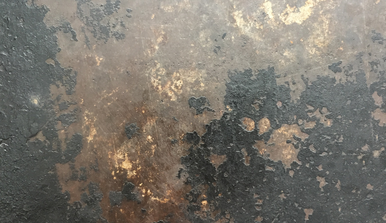 A detailed image of a roasting tin, showing natural patina of wear