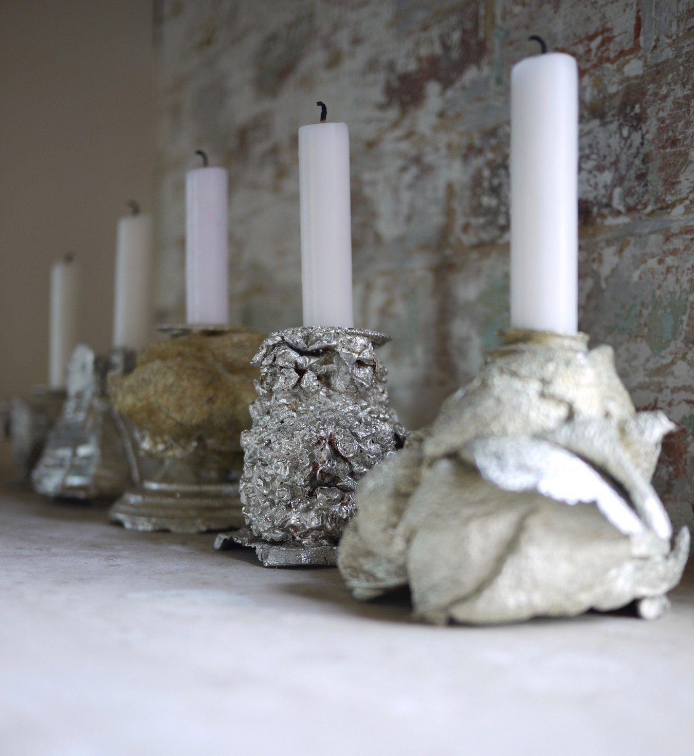 Image of 5 cast pewter candlesticks. The packaging material has been kept wrapped around the silver candlestick a mould made and a casting of the wrapped candlestick then produced equalling all materials to one; pewter