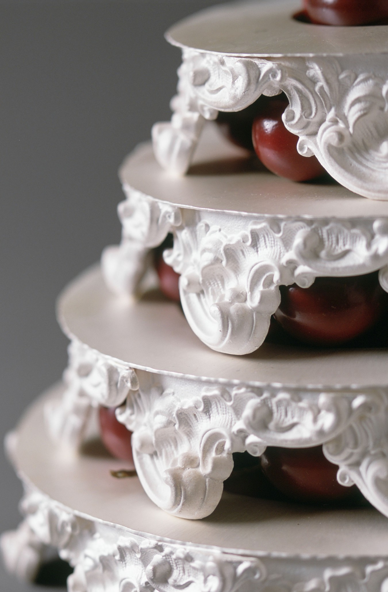 Image of a 4 tiered wedding cake made from cast highly ornate tray legs. The silver is white cooked resembling royal icing