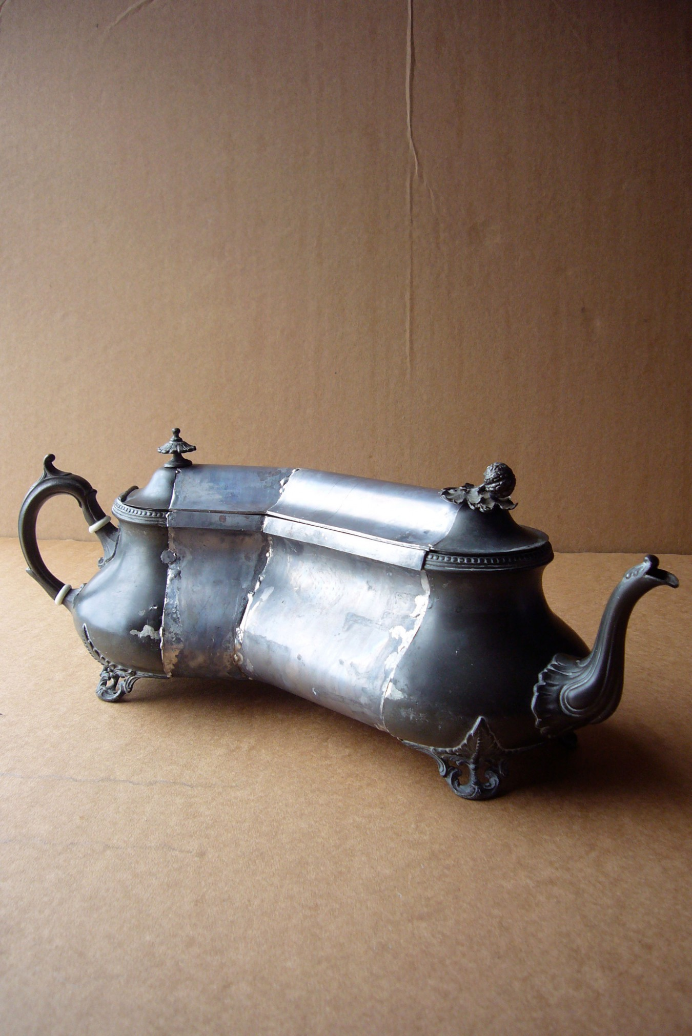 Image of an old tarnished metal teapot, cut altered placed in a new configuration with the addition of lead which robs the teapot of it's original function