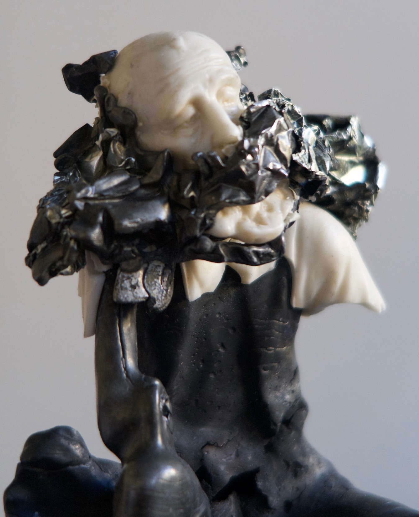 Image of a white porcelian figure of an old gentleman sitting down. The slipcast figure has been filled with molet pewter and resulting explosion recorded. The petwer core has been patinated black