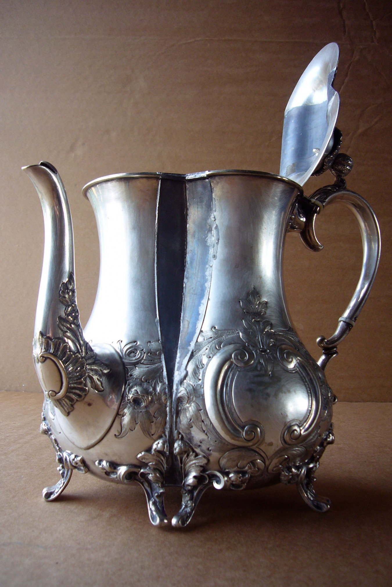 Image of a silver plated baroque coffee pot. Vertically spliced open and an insert of lead soldered in, the original feet become pigeon toed and the lead suggests a cleavage.