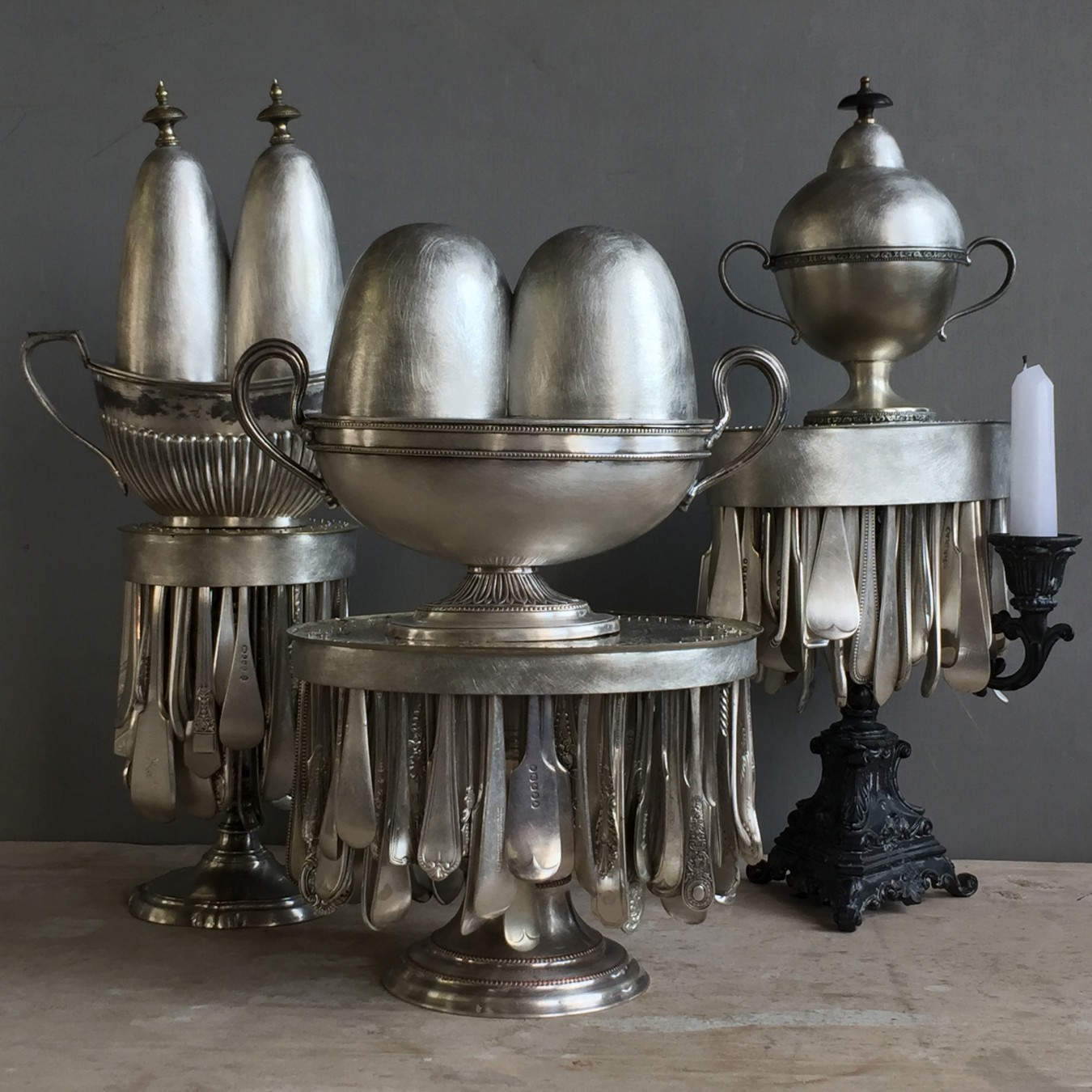 Image of 3 treasure boxes on stands. Using old candlesticks as bases, cutlery handles added as fringes that move. Old sugar bowl included and each given crazy lids that are historically dull and boring.