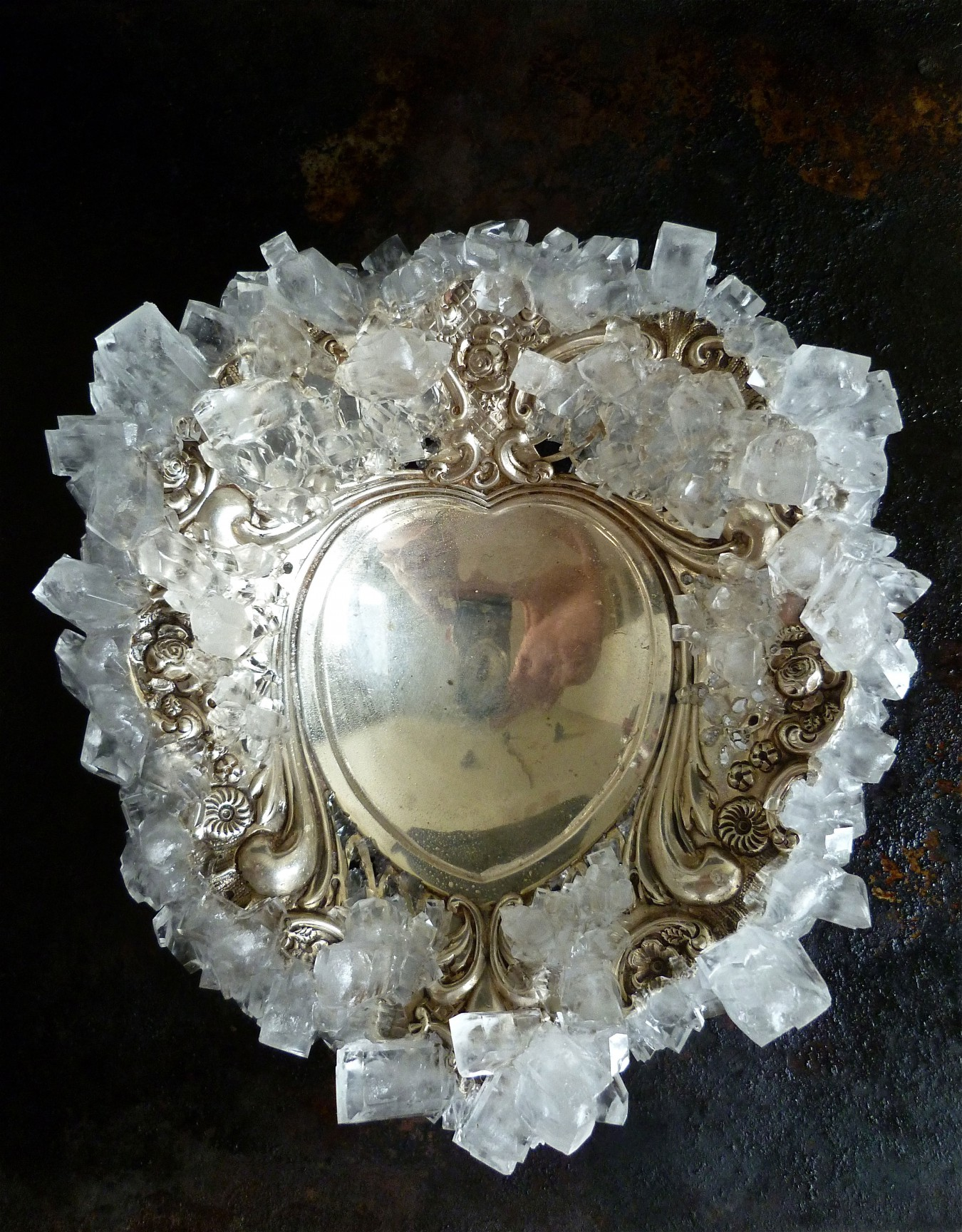 Image of a solid silver heart shaped bonboniere dish made sweeter by growing sugar crystals around and through the edge of the piece