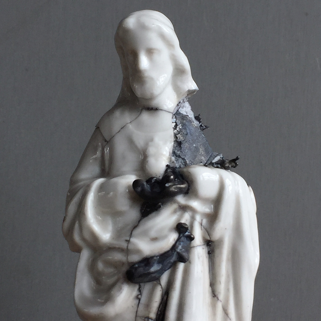 Detailed image of a white ceramic statue of Jesus. Cracked and broken showing an inner core that is patinted black.