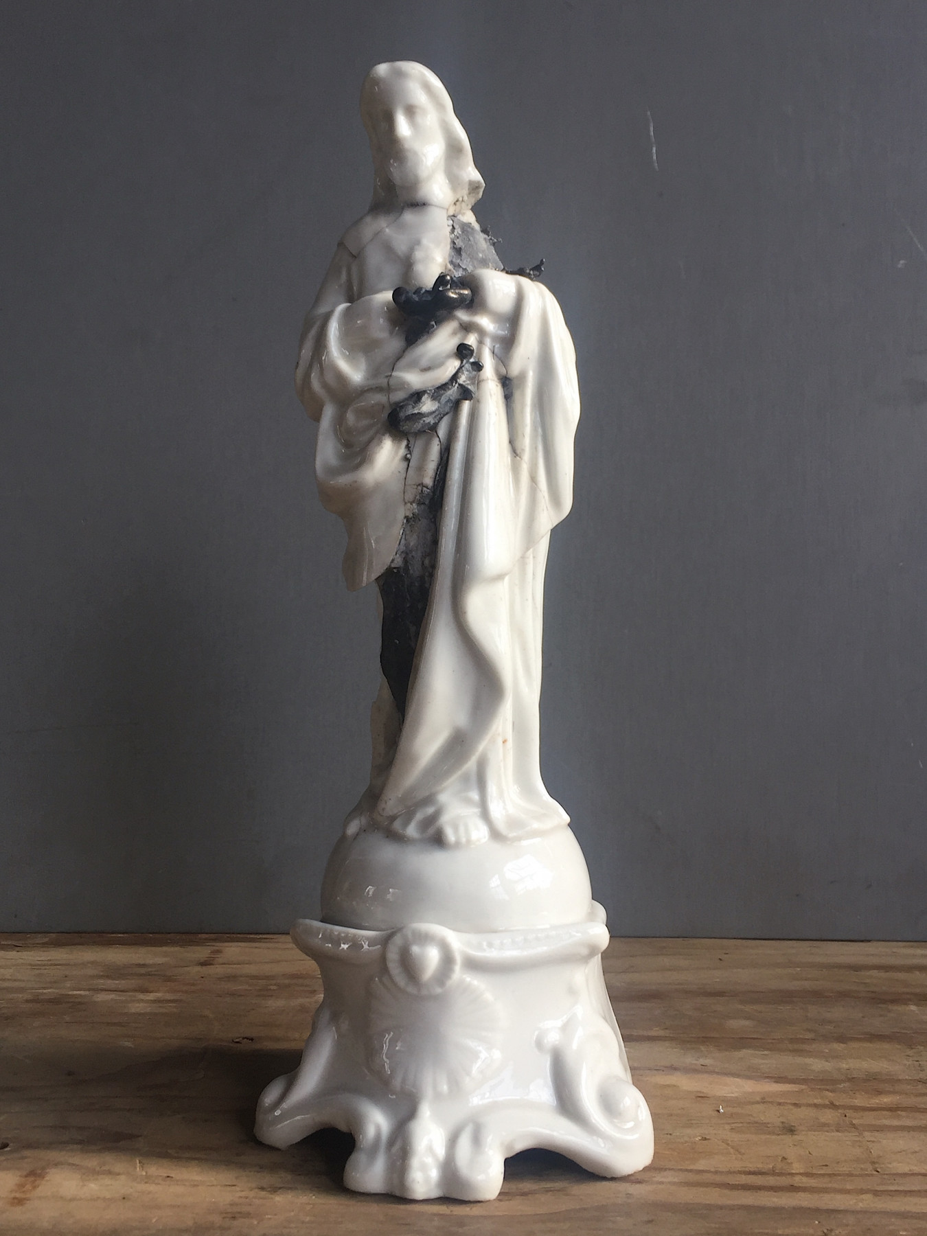 Image of a white ceramic statue of Jesus. Cracked and broken showing an inner core that is pewter and patinted black.