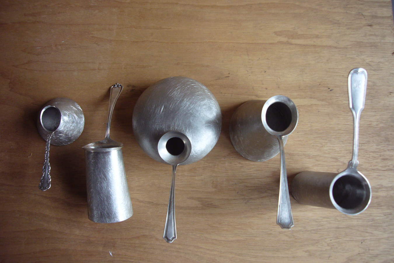 Image of a series of extended and exaggerated metal spoons, playig with a tool that is used for measuring ingredients in the kitchen