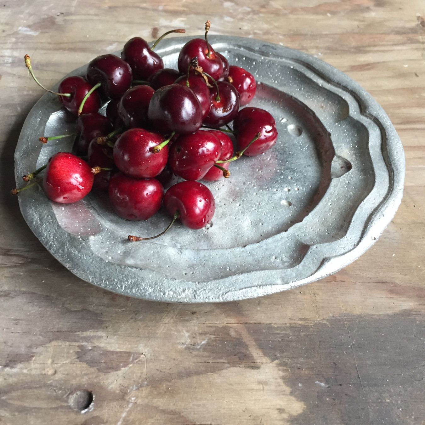 Image of a pewter plate with fresh cherries.