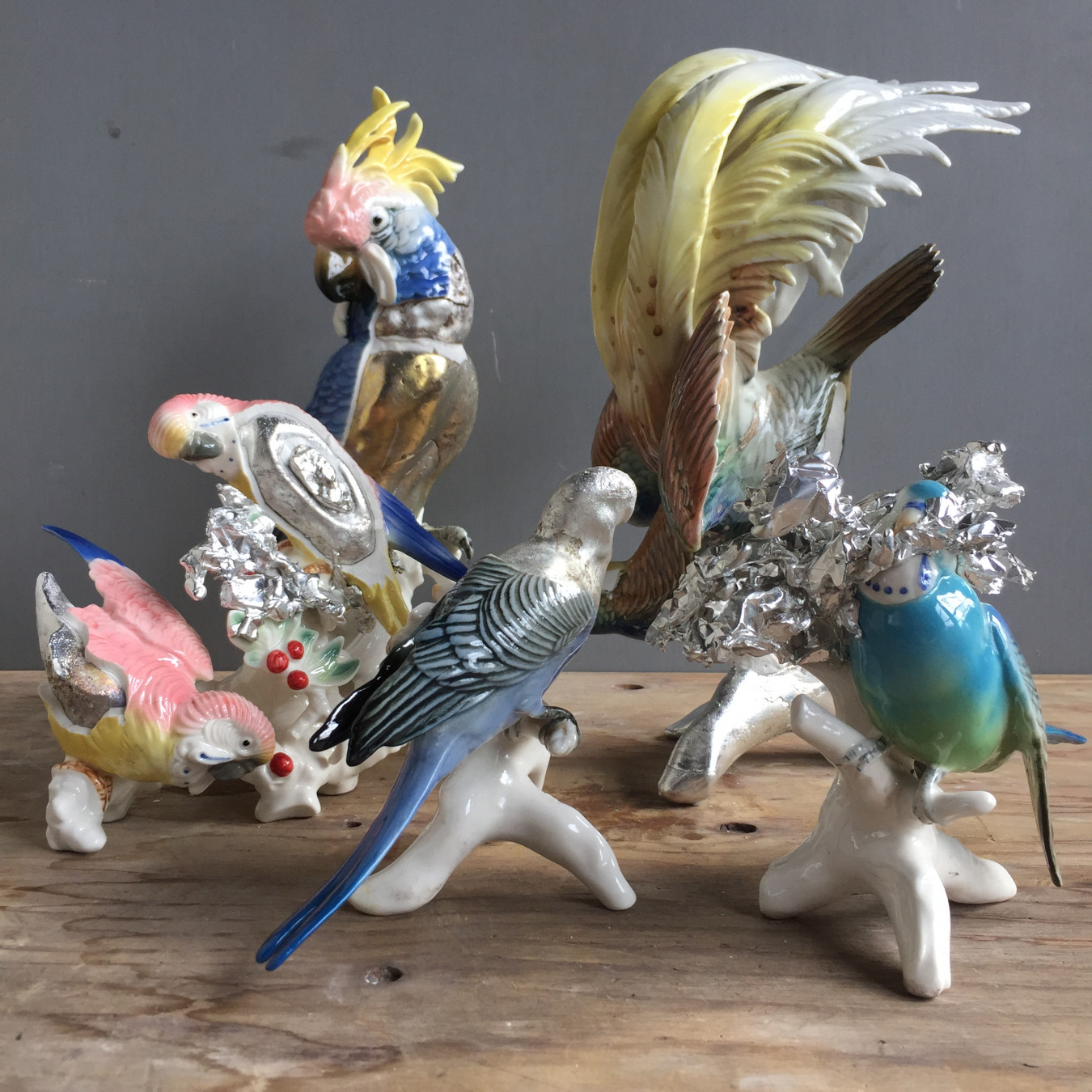 Image of a group of exotic ceramic birds made be Karl Erns, these have been altered by pouring molten pewter into the hollow parrots and budgies