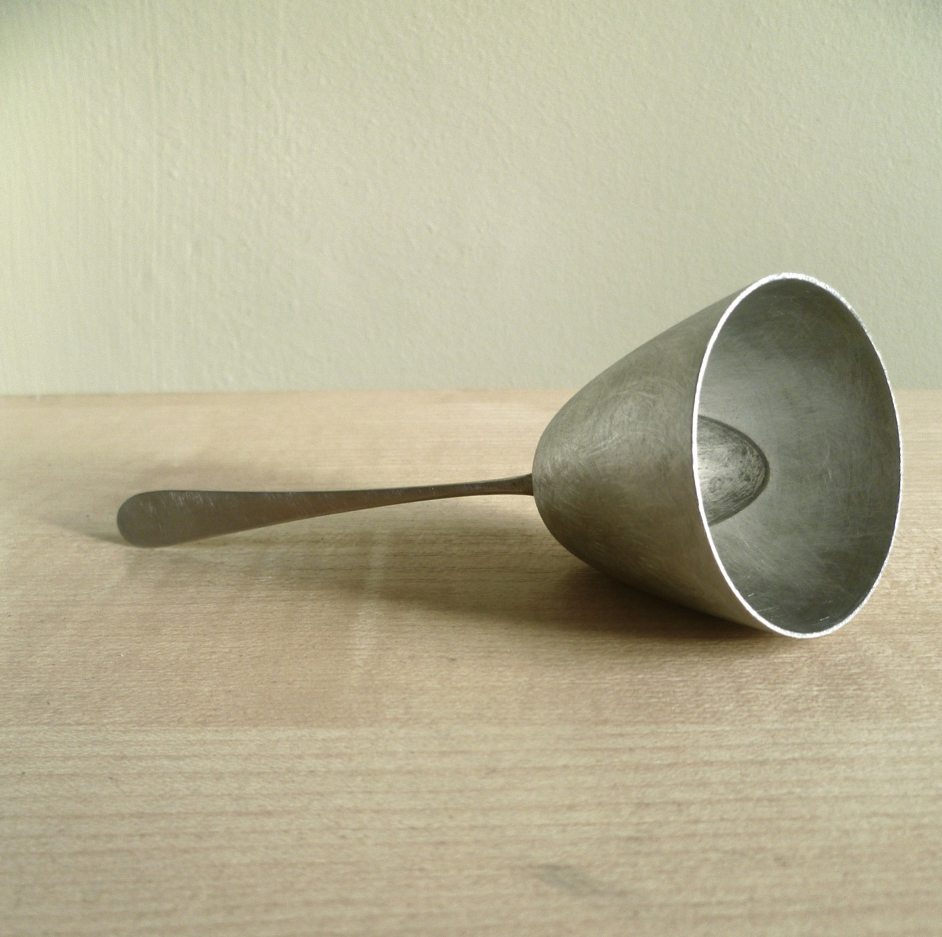 An image of a metal tear catcher made from an adapted spoon. In a resting position.