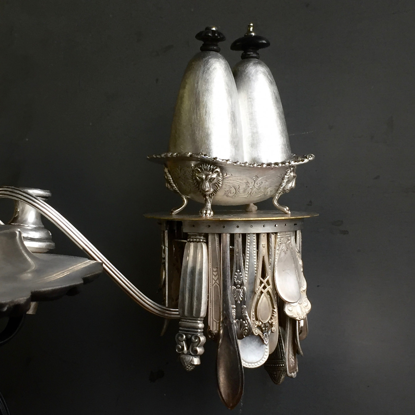 Detail image of a small salt cellar that has been altered and given a fancy lid, sitting on a platform fringed with cultery.