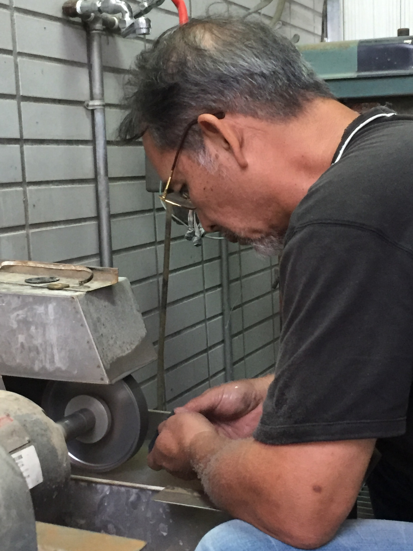 Image of A-Fu working at a machine to grind stone. Stone residency NTCRI Taiwan.
