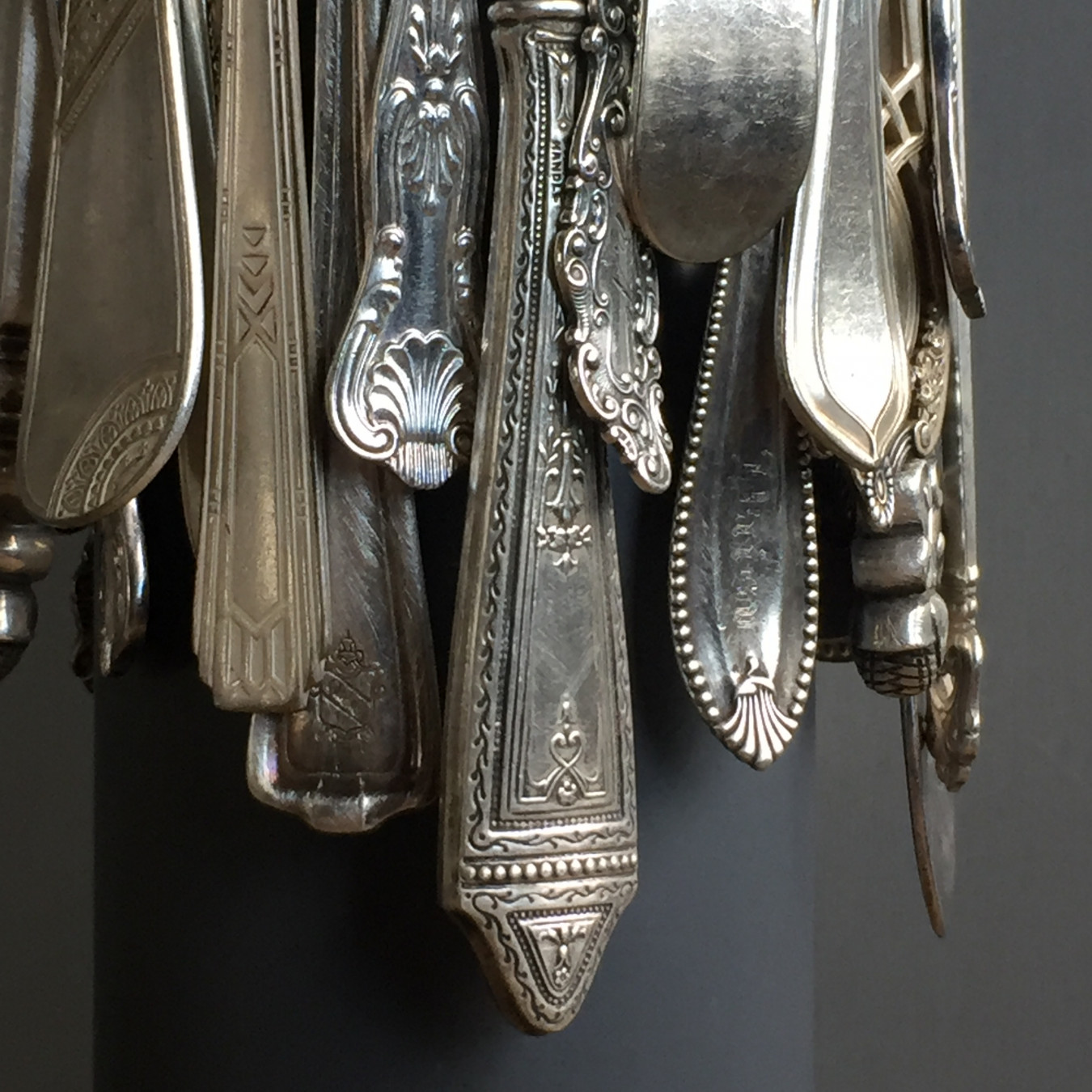 Detail image of the donated cutlery which has been bought together to create a fringed 'platform'.