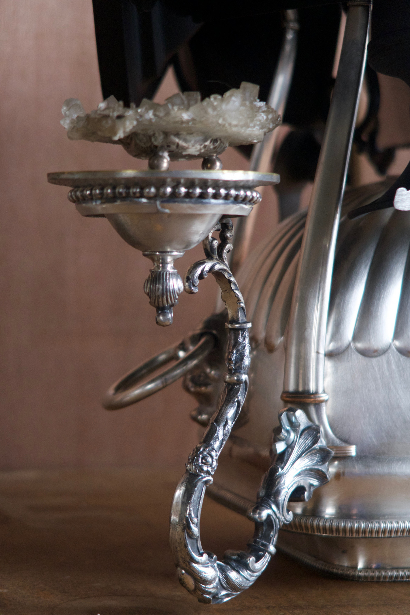 Detail image of a silver sugar sweetheart dish, presented on an arm that extends out from the main body of the centrepiece.