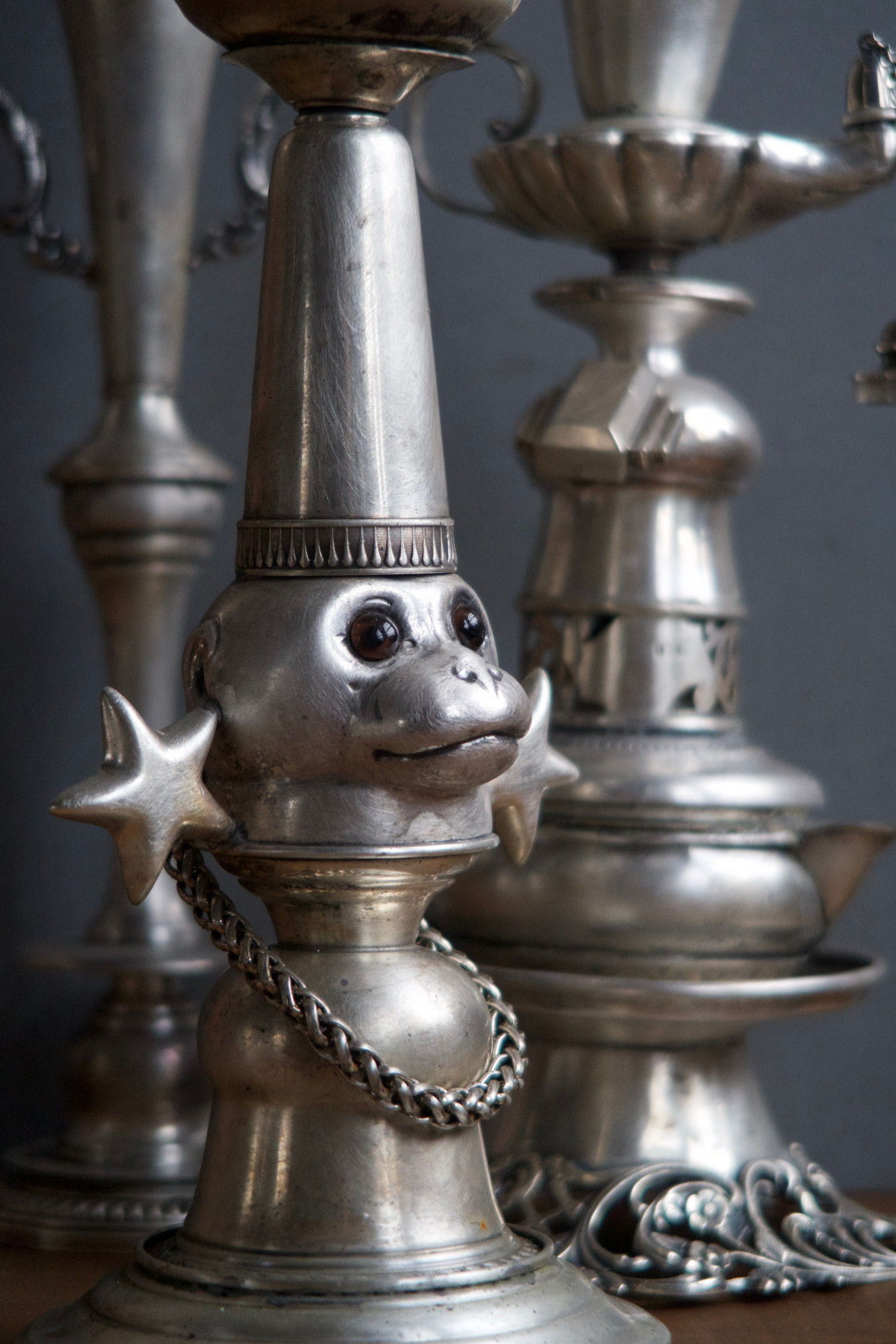 Detailed image of candlesticks made up of Tiffany earrings, a monkey bottle stopper and other pieces of silverware stacked up and soldered together to form tall towers.